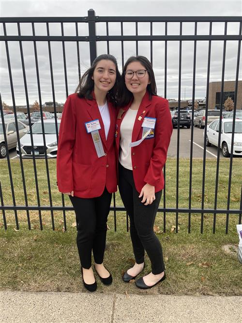 Two young women pose in red blazers