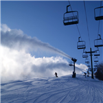 Single Skier comign down hill with Snow blowing and chair lift
